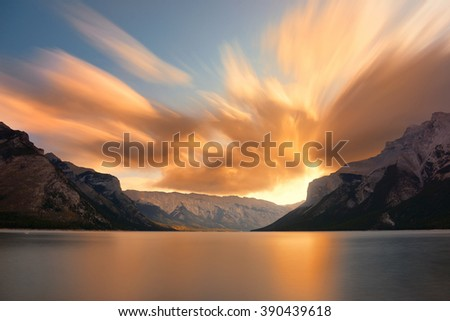 Lake Minnewanka in Banff national park with mountains and forest in Canada at sunrise. - stock photo