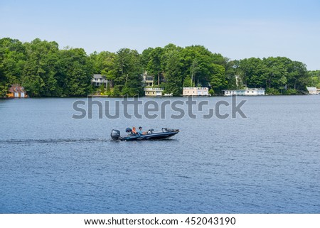 Lake Muskoka, Ontario - July 11, 2016: An unidentified couple in a sleek power boat driving along the row of boathouses and cottages on shoreline of Lake Muskoka in Ontario