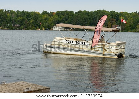 LAKE MUSKOKA,ONTARIO - SEPT 7: Small pontoon cruise boat plying on Lake Muskoka on September 7, 2015. Lake Muskoka is the largest of three interconnected lakes in the Muskoka region, north of Toronto. - stock photo
