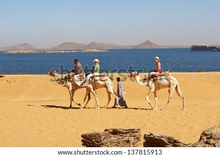 LAKE NASSER, EGYPT-NOV 28:Tourists ride camel in desert toward ruined temple of Dakka. The ancient Egypt Ptolemaic temple dedicate to Thoth of the Sycamore Fig. Nov 28, 2007. Lake Nasser, Egypt.