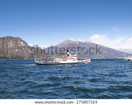 Lake of Como, Italy - April 1, 2015:  A passenger boat service on the lake approaching tourist boarding.