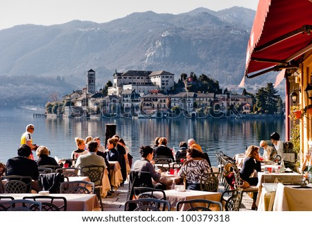 LAKE ORTA, ITALY - FEB 24: People in a restaurant in Orta on February 24, 2012. With the nearby Unesco site Sacro Monte and San Giulio island, Orta is a popular destination for small-scale tourism. - stock photo