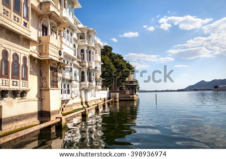Lake Pichola with residential houses at cloudy sky in Udaipur, Rajasthan, India - stock photo