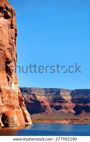 Lake Powell landscape majors in red sandstone cliffs.  Vivid blue water reflects vivid blue sky.