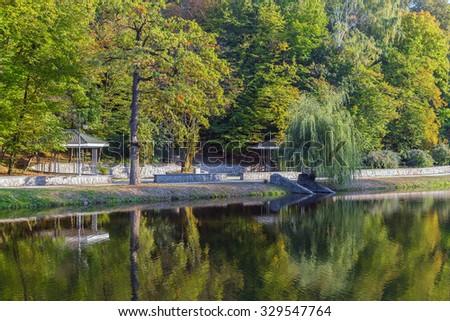 Lake reflections of fall foliage. Colorful autumn foliage casts  - stock photo