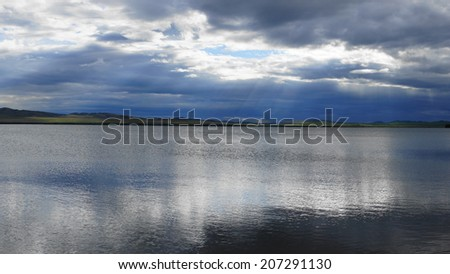 Lake Shira (Khakassia) evening view. Dark cumulus clouds reflecting on the still water surface. Natural landscape, July 17, 2014. - stock photo