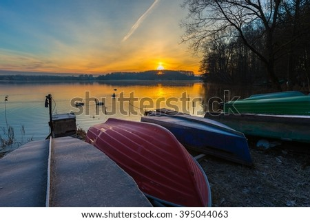 Lake shore with fisherman's boats. Beautiful magic sunrise over lake.