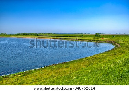 Lake shore with green grass on sunny day, Holland, Netherlands, HDR - stock photo