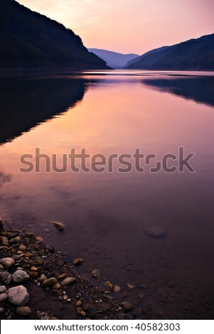 lake shore with stones after sunset - stock photo
