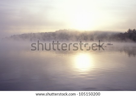 Lake Shrouded in Autumn Morning Fog, Squam Lake, New Hampshire - stock photo