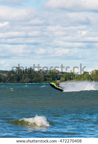 Lake Simcoe, Ontario - August 21, 2016: An unidentified jetski enthusiast is driving his jet ski across big waves at the Lake Simcoe and using a wave as a ramp to jump high in the air