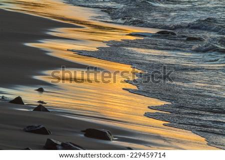 Lake Superior, Michigan - September 30, 2011:  waves reflecting sunset on the shore of Lake Superior - stock photo