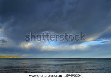 Lake Superior, rainbow, and clouds at Porcupine Mountains Wilderness State Park, Michigan's Upper Peninsula, USA  - stock photo