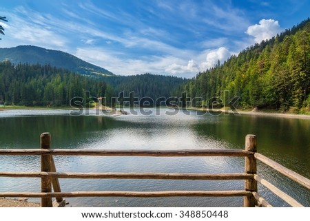 Lake Synevir summer in Ukraine. Decorative fence in the foreground.