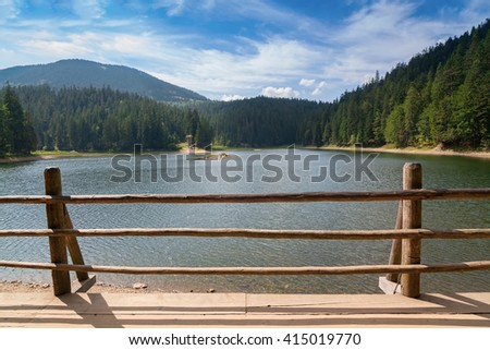 Lake Synevir summer in Ukraine. Decorative fence in the foreground. - stock photo