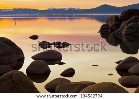 Lake Tahoe Sunset with granite boulders. - stock photo
