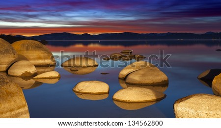 Lake Tahoe Sunset with granite boulders. - stock photo