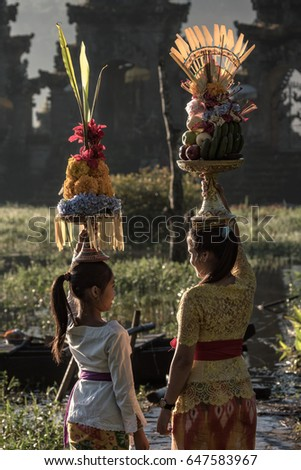 Lake Tamblingan, Tabanan, Bali, Indonesia - May 12, 2017 : Balinese girls carrying the ceremony offerings on their heads