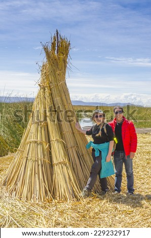 Lake Titicaca, Peru - Couple of tourists poses near reed bundle on one of floating islands