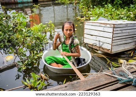 LAKE TONLE SAP, COMBODIA - SEP 28, 2014: Unidentified Vietnamese girl sails with a snake in a pelvis on a Tonle Sap Lake, the largest freshwater lake in Southeast Asia, a UNESCO biosphere since 1997
