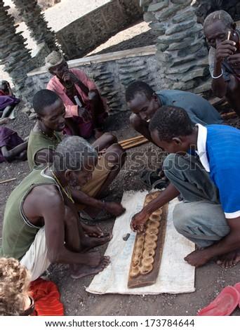 LAKE TURKANA, KENYA - JANUARY 12: El molo men playing  traditional game. January 12, 2013 in Lake Turkana.  - stock photo