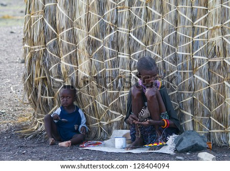LAKE TURKANA, KENYA-JANUARY 12: El molo woman and unidentified child make traditional necklace January 12, 2013 near lake Turkana, Kenya. The El molo are one of the disappearing tribes of Africa. - stock photo