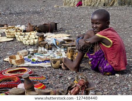 LAKE TURKANA, KENYA-JANUARY 12: Unidentified El molo child sells traditional souvenirs January 12, 2013 near lake Turkana, Kenya. The El molo are one of the disappearing tribes of Africa. - stock photo