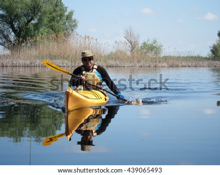 "LAKE ""VEREGA"", UKRAINE -APRIL 23, 2016: Kayaking in calm blue lake. Man in yellow kayak and red rescue jacket on the calm blue lake in early spring in sunny day"