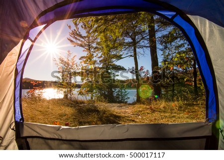 Lake view from inside of a tent . Camping upstate New York. Sunset light, lens flare. The Catskills are one of the most popular destination for scenic drives, bike trails, foliage and nature lovers.