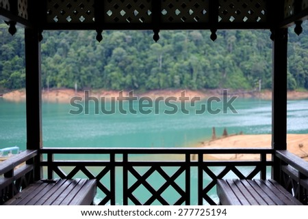 Lake view inside wooden gazebo overlook the tropical forest island.  - stock photo