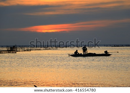 Lake view with fisherman on  colorful boat in morning time:select focus with shallow depth of field. - stock photo