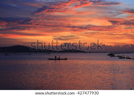 Lake view with fisherman on colorful boat in morning time select focus with shallow depth of field.  - stock photo