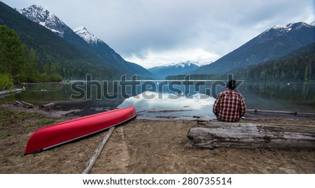 Lake with a canoe and man looking while sitting on a log - stock photo