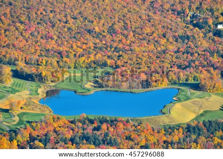 Lake with Autumn foliage viewed from mountain top in New England Stowe - stock photo