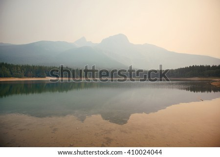Lake with fog and mountain reflections - stock photo
