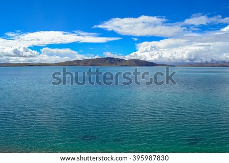 Lake with mountains and clouds as background