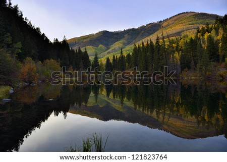 lake with reflection of the mountains and golden, green and red aspen in Colorado during foliage season - stock photo