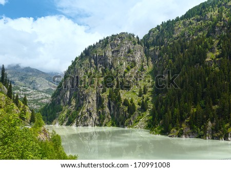 Lake  with turbid water formed the dam. Summer mountain landscape (Alps, Switzerland)