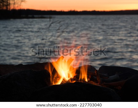 Lakeside campfire burning in flames at lakeside during sunset