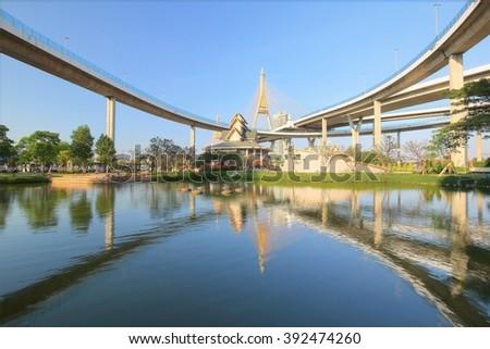 Lakeside scenery under Bhumibol Bridge (or Industrial Ring Road Bridge) with view of elevated highway interchange & bridge tower reflecting on smooth lake water in Lat Pho Park, Bangkok City Thailand - stock photo