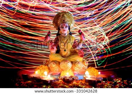 Lakshmi - Hindu goddess, Goddess Lakshmi. Clay diya lamps lit with Goddess Lakshmi during Diwali Celebration. Greetings Card Design Indian Hindu Light Festival called Diwali - stock photo