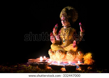 Lakshmi - Hindu goddess, Goddess Lakshmi. Clay diya lamps lit with Goddess Lakshmi during Diwali Celebration. Greetings Card Design Indian Hindu Light Festival called Diwal - stock photo