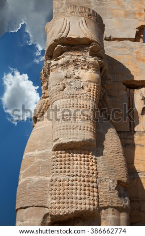 Lamassu, the bull with head of a bearded man, guarding the entrance Gate of All Nations in the ruins of Persepolis in Iran against blue sky with dramatic bright white clouds. - stock photo