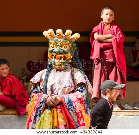 Lamayuru, India - June 17, 2012: monk performs a religious masked dance of Tibetan Buddhism, children monks carefully watching the ritual during the Cham Dance Festival in the Lamayuru monastery. - stock photo