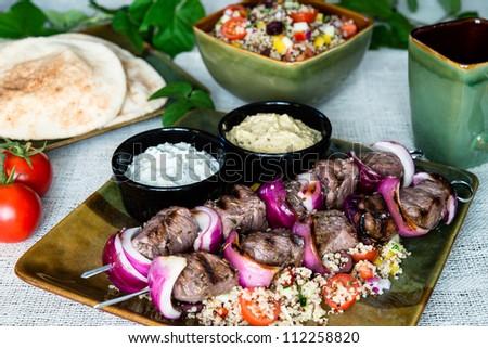 Lamb beef kebab skewers grilled with quinoa salad, pita bread, and tzatziki and hummus sauce - stock photo