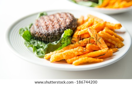 Lamb Burger Patties Served with Lettuce and Sweet Potato Fries for Healthy Gluten and Dairy Free Meal - stock photo