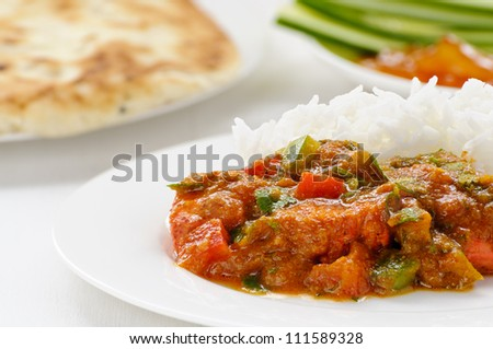 Lamb jalfrezi, a meat curry with red and green peppers, with naan, cucumber and mango chutney behind - stock photo