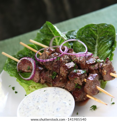 Lamb kebabs with tzatziki yogurt and red onions. - stock photo
