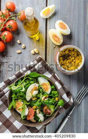 Lamb lettuce salad with eggs, roasted nuts, mozzarella and corn - stock photo