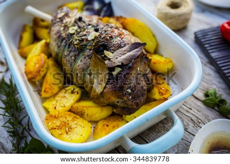 Lamb meat - roasted leg of lamb with rosemary, spices and roasted potatoes - stock photo